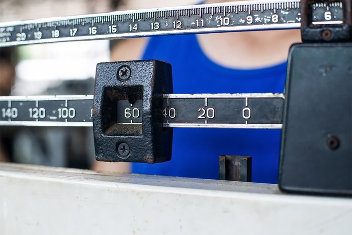 Being weighed on a scale.